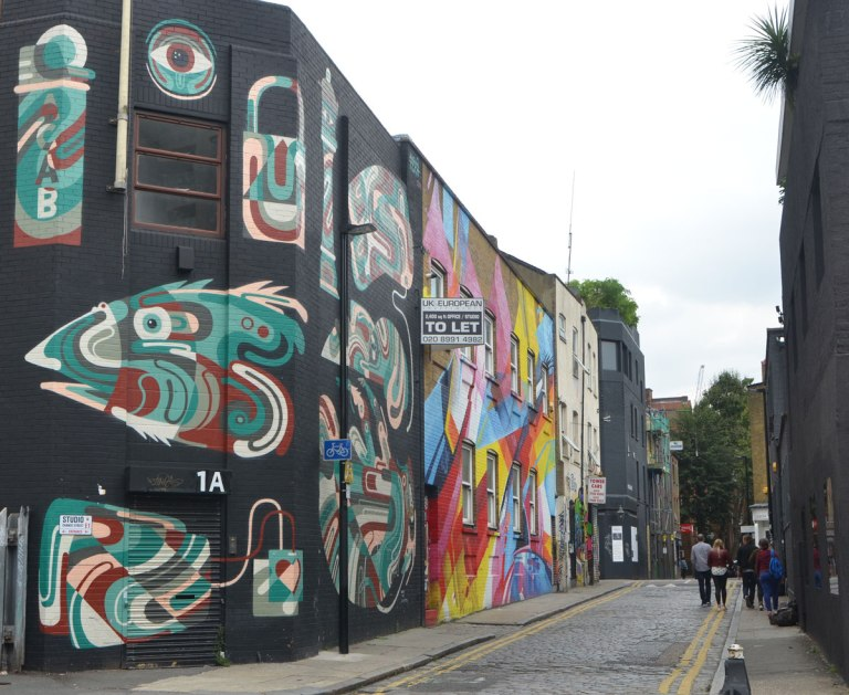 looking down Chance Street in Shoreditch, a few people walking on the narrow street, the buildings on the left are covered with murals. The first is aboriginal symbols in white, green and brown on a black background. THe second is in bright shades of blue, red and yellow.