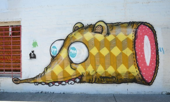 graffiti street art on a white wall - front end of yellow creature with big ping pong ball like eyes