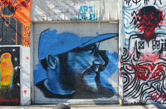 street art painting on a metal roll up garage door of a man in profile, in black and blue