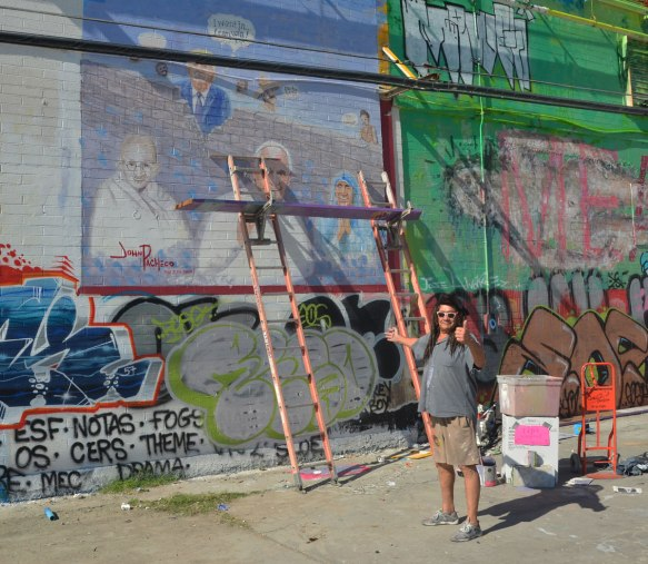 street artist John Pacheco stands in front of the ladder that he is using to paint a mural featuring Donald Trump, Ghandi, the Pope, Mother Theresa and a wall that is being built.