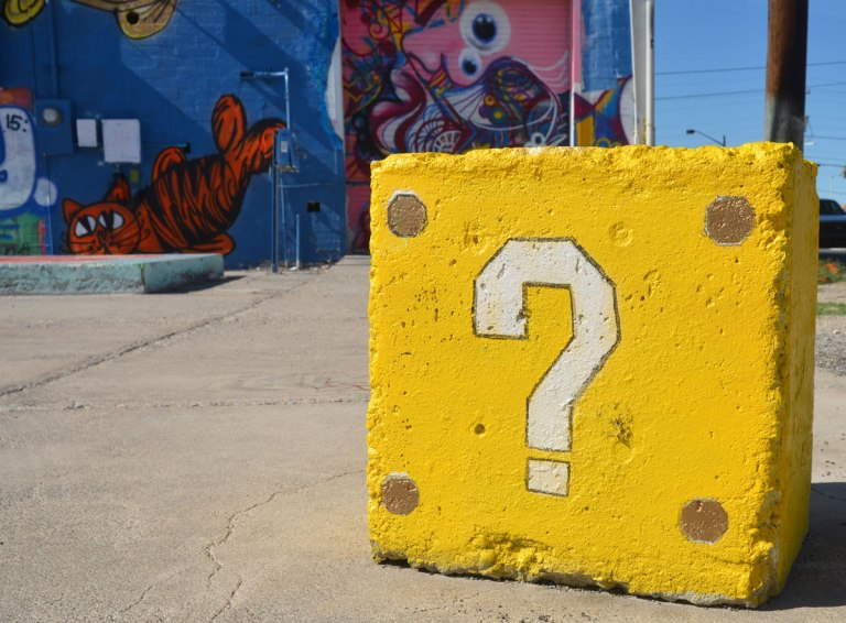 white question mark on a concrete block painted yellow, with a mural covered on a wall in the background