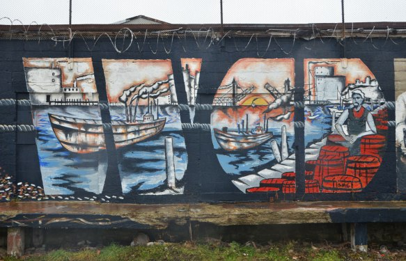 part of a larger mural, a dock scene, harbour, ship in the water, lift bridge open in the background, kegs and barrels on the dock, a man working on the dock