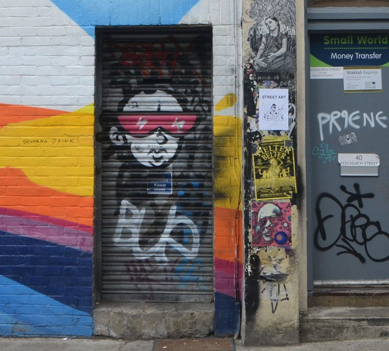 graffiti on a black metal door, a face with big red glasses