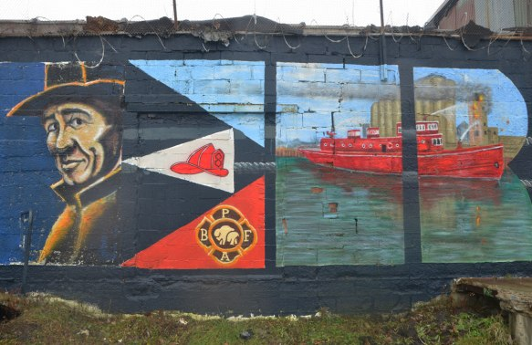 part of a large mural celebrating the workers of Buffalo, this panel is for the police and firemen and includes a red fire boat.
