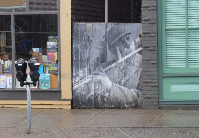 black and white photo of a man playing the flute, pasted onto a woodedn fence beside a sidewalk, next to a book store, a parking meter nearby, on a street in Buffalo