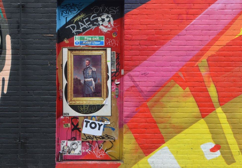 a door with pasteups on it, between a black wall and a wall that is painted in red, pink and yellow.