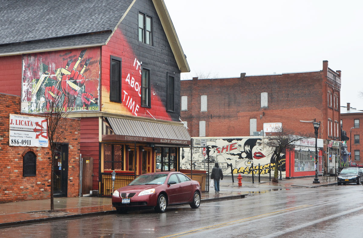 a brick two storey store with a mural on the upper part in red, yellow and black, with the words It's about time. The picture in the mural is three red fists. One is holding a yellow paint roller and one is holding a yellow spray paint can. Another mural is in the background, a car parked on the wet street, a pedestrian on the sidewalk