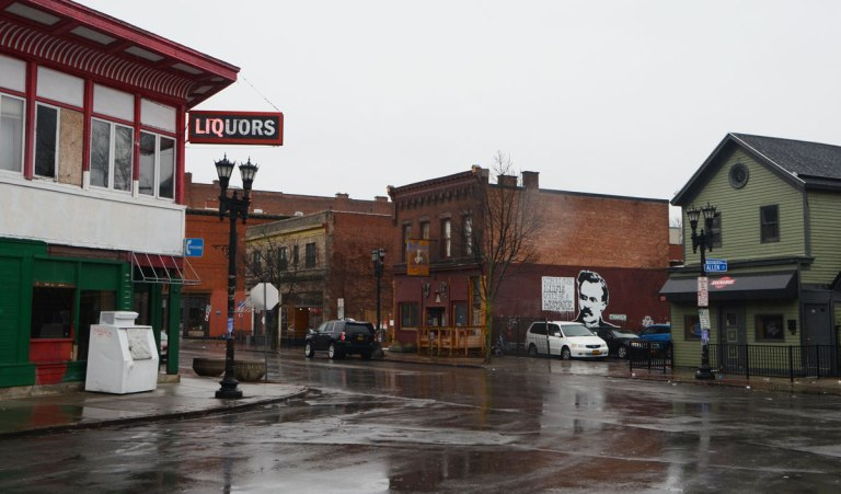intersection in Buffalo with old two storey square front storefronts. wet road, rainy day, liquor store on the corner that is now empty but the sign only half works - only half the letters in the word liquor are lit.