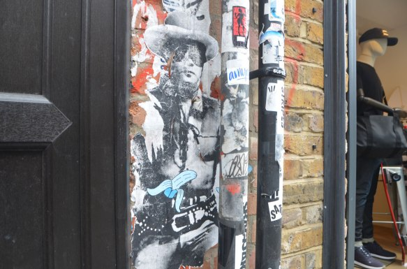 a pasteup of a black and white print of a cowboy, not quite life sized, with cowboy hat and vest. The paper is starting to peel away at the edges. A sticker of a blue and white partially peeled banana has been stuck on him. Beside him is a male mannequin in a store window.