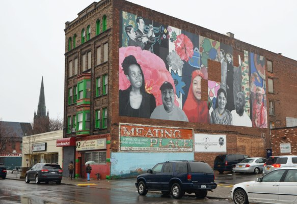 5 storey brick building on Grant St in Buffalo, with green trim around the windows and a small parking lot beside, sign on the side of the building says Meating Place. There is a large mural on the side of the building featuring realistic portraits of many people, including two trumpet players, a girl in a red head scarf, and other men and women,