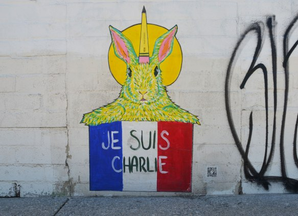 graffiti street art on a white wall - a yellow rabbit with a pencil behind its ear, holding up a french flag with the words je suis charlie on it.