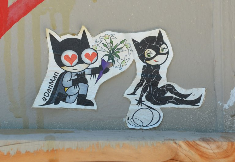 graffiti street art on a white wall - a sticker by Danman of a man and a woman in cat suits. The man has hearts in his eyes and is presenting the woman with some flowers