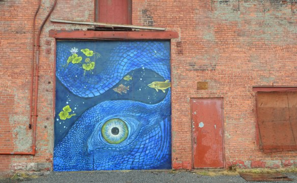 blue mural on an industrial building door, blue marine scene feathuring a large close up of an octopus eye and part of its body, along with some yellow fish, some lily pads and a water lily flower