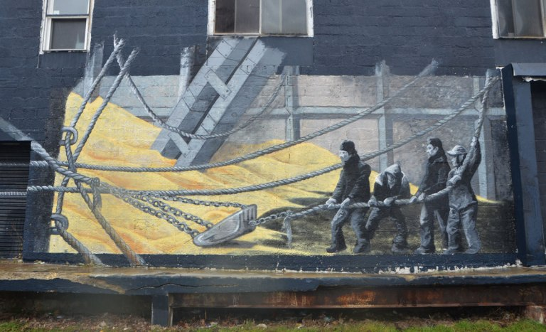 part of a larger mural, men hauling a rope and filling a shovel with wheat