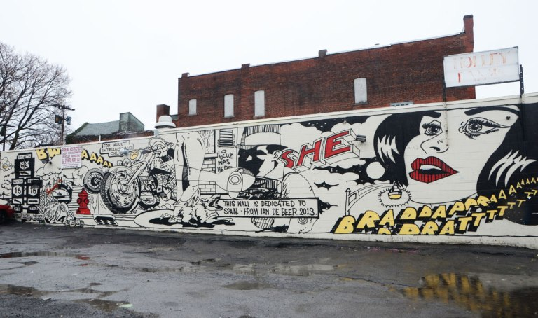 long horizontal mural drawn like a comic book strip, dedicated to the memory of Spain Rodriguez and painted by Ian DeBeers in 2013, a large woman's face with bright red lips, the word 'she; painted in red, a motorcylce, a man wearing a hat,