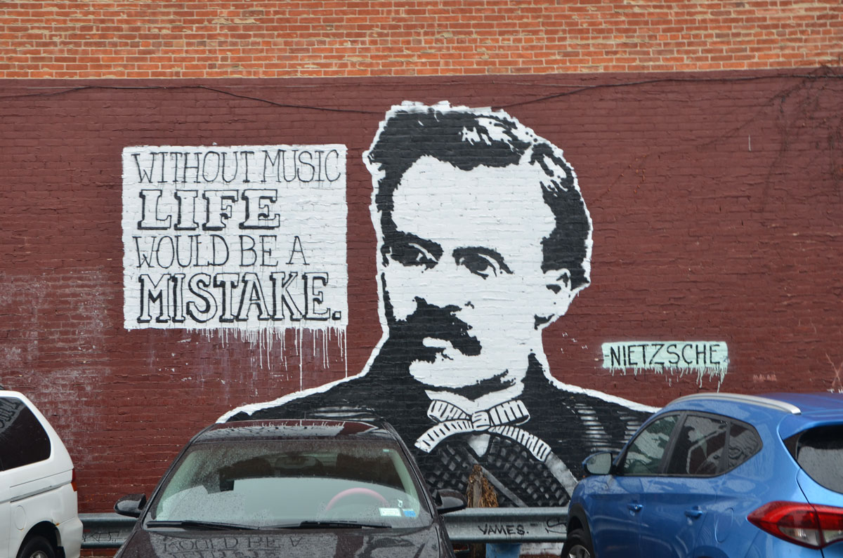 street art picture of Nietzsche head and shoulders in black and white along with a quote that says Without music life would be a mistake.