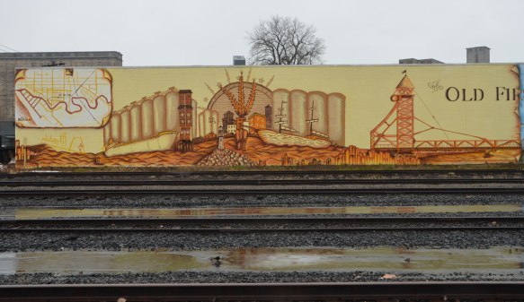 mural about the Old FIrst Ward, Buffalo. involves two large panels, one is an image from the past with grain and grain elevators and the other is a scene from the present with the area as a residential parkland with old grain elevators in the background. Railway tracks run in front of the mural.