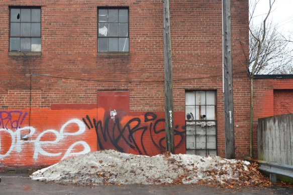a red brick building, side of a store, bottom part has been painted orange, probably to paint over graffiti, but has since been tagged twice, once in black and once in red, a parking lot is in front of the wall, with a small snowbank at the edge.