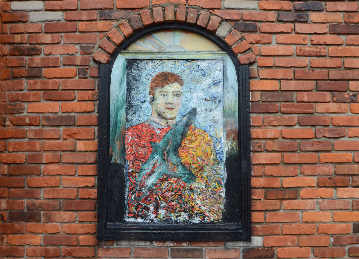 a painting of a man has been mounted in an arched window, covers the window.