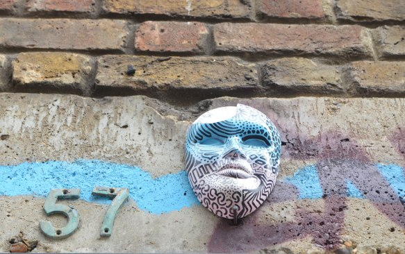 a 3D mask graffiti piece mounted high on a wall, painted in white, turquoise and purple patterns. The number 57 is beside it.