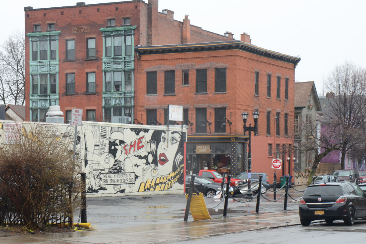 mural in the middle gound, two low rise buildings in the background, one is the Puritan building with green details around the windows in the front of the building.