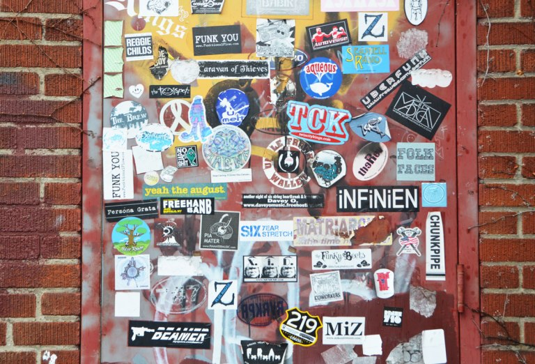 a door is covered with graffiti stickers.