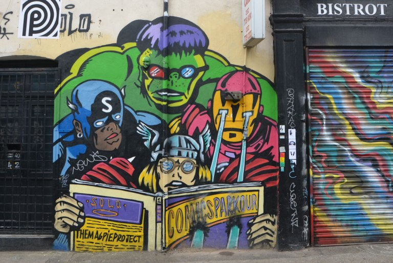 a group of comic book heros is reading a comic book together, The Hulk, a man with laser vision, Thor, and a man with a blue costume and an S on his hood.