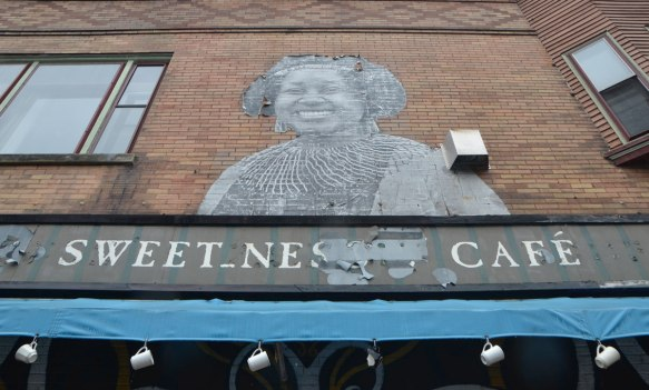 a large, life sized or larger, paste up of a drawing of the head and shoulders of a black middle aged woman, smiling, above the awning for the Sweetness cafe.   6 white mugs hang from hooks through holes along the lower edge of the awning