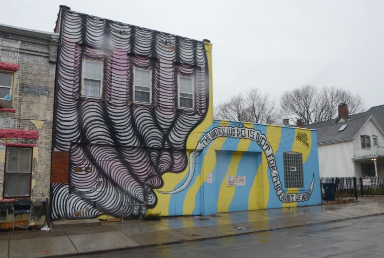 a mural on the side of a building. On the left is a purple and black drawing of what looks like fingers. on the right are yellow and turquoise stripes with the words, the work we do is not for the faint of heart