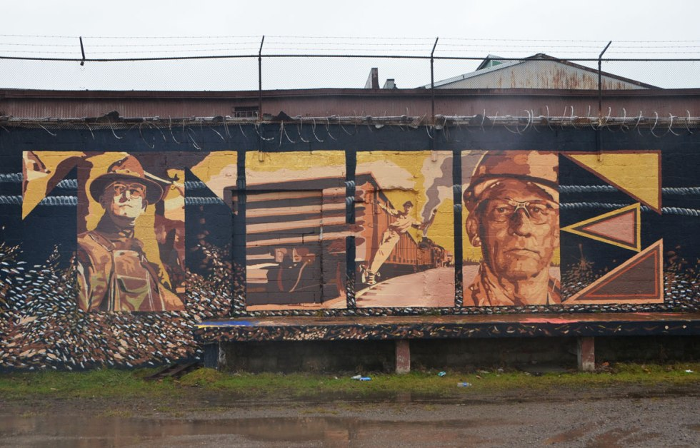 part of a larger mural called The Worker, with the words Thw WOrker written in large capital letters and filled in with pictures of working people. Along the side of a wall beside a train track