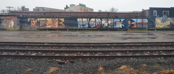 a long horizontal mural called The Worker, with the words Thw WOrker written in large capital letters and filled in with pictures of working people. Along the side of a wall beside a train track - view of whole mural with tracks in the foreground