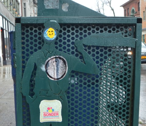 part of the side of a green metal container for recycling bins on a Buffalo sidewalk, relief sculpture of a man on the side, to which someone has added to sticker, one is a happy face sticker on the head and another is a parody of wonder bread that says sonder.