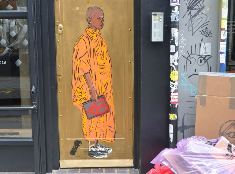 a streeet art pice on a door, a person in a long orange robe is standing, holding a sign with a red peace symbol on it. A work by unify