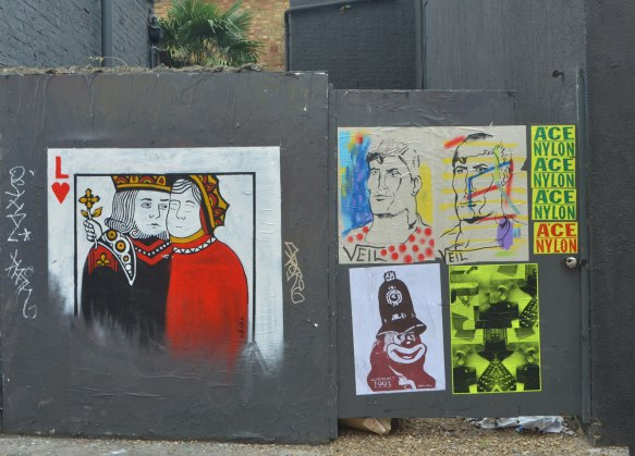 5 pasteups on a grey wood fence. On the left a playing card of two people cheek to cheek with an L and a red heart. Also two drawings, portraits of men, by veil,