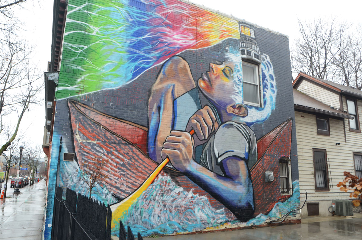 a mural called Voyage painted by Chuck Tingley on the side of a building in Buffalo, a large multicoloured boy is sitting in a small boat and holding on to a yellow paddle. The sky is rainbow colours.