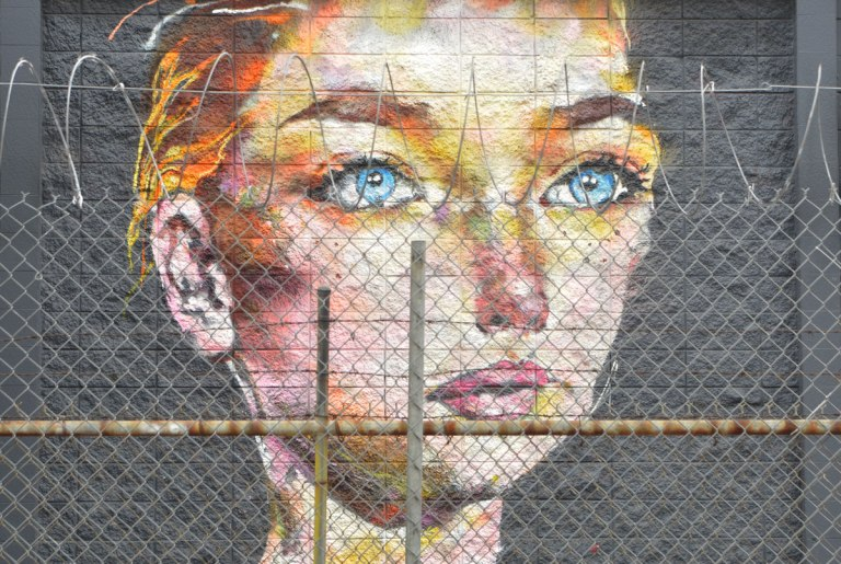 realistic mural of a woman with short blond face and blue eyes, staring straight ahead, head and neck only, on a black wall, seen from the other side of a wire fence with looped barbed wire across the top.