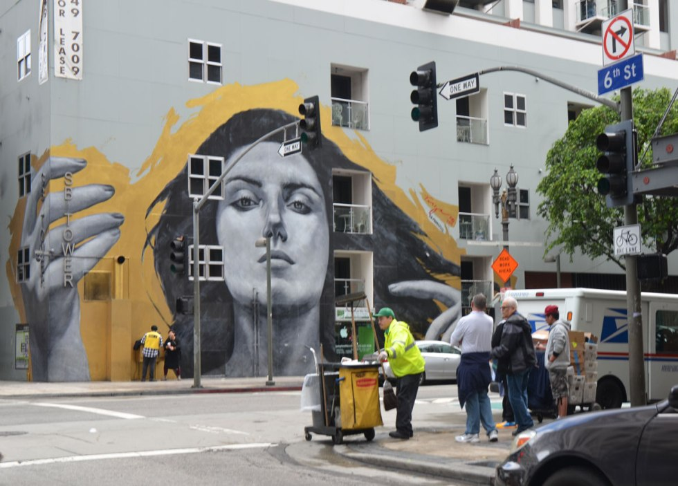 large mural of a woman's head in monochrome grey, almost three storeys tall, surrounded by yellow, with a large hand wrapped around the corner of the building, photo taken from diagonally across the intersection. A man in yellow jacket is pushing a cart, a street cleaner, as he starts across the intersection. Other people are waiting for their green light.