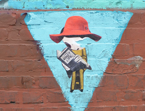 paste up graffiti on the wall of the Angel City Brewery - a seated phoebe from new york reading a book, she's wearing a large red hat
