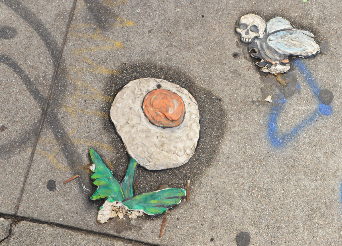 a flower picture, graffiti on the sidewalk, green leaves and stem, the flower part is a sunny side up egg, hovering over the flower is a bird with a human skull instead of a head