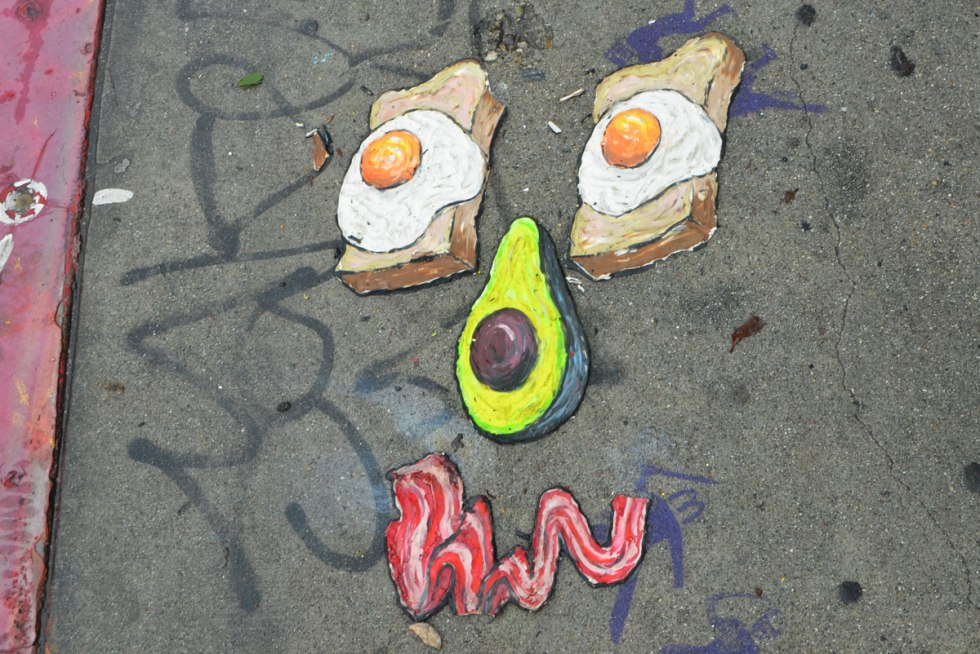 artwork on a sidewalk, making a face, are 2 eggs sunny side up on slices of toast for eyes, the nose is half an avocado with the pit still in, and the mouth is a piece of bacon, all 3D