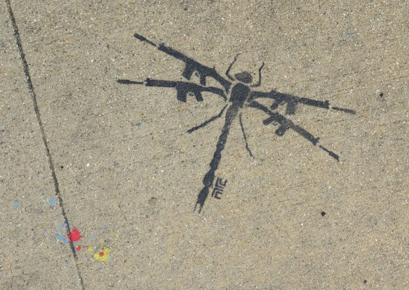 black stencil on grey concrete sidewalk, a dragonfly with wings made of automatic rifles.