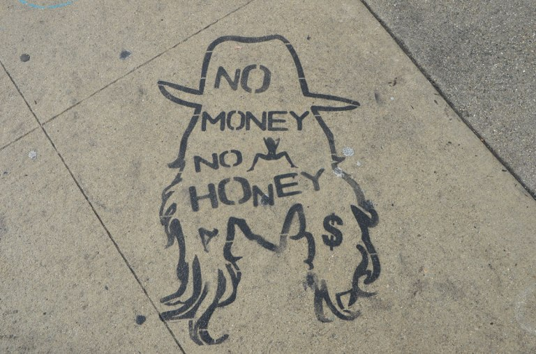 black stencil on grey concrete sidewalk, outline drawing of a man with long hair and a cowboy hat, with words written inside the drawing that say No money no honey.