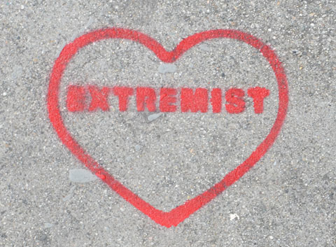 red stencil on grey concrete sidewalk, outline of a heart with the word extremist written inside it.