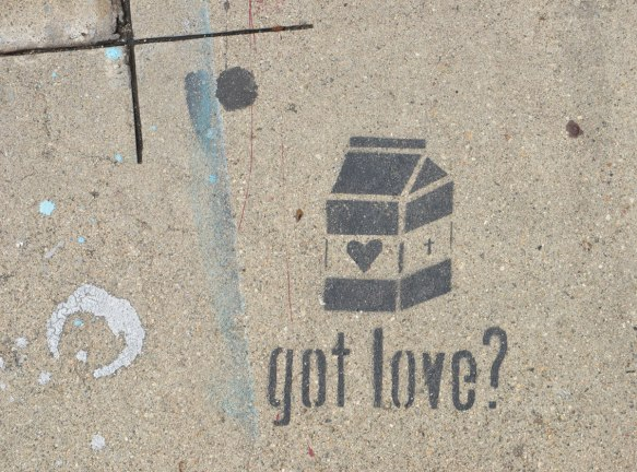 black stencil on grey concrete sidewalk, of a small milk box with a heart on the side. Words written underneath are got love?