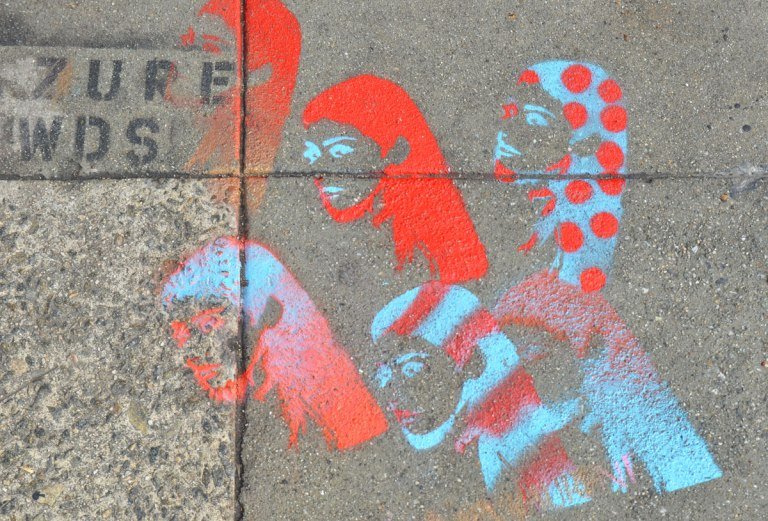 Stencils on the sidewalk, spray paint, in red and turquoise, the heads of 6 women in head scarves, shown in profile, One is in a scarf that is turquoise with red polka dots and one has red and turquoise striped pattern on her scarf.