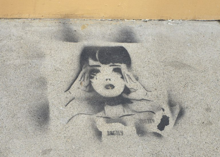 black stencil on grey concrete sidewalk, shoulders and head of a young woman with her hands up to her face