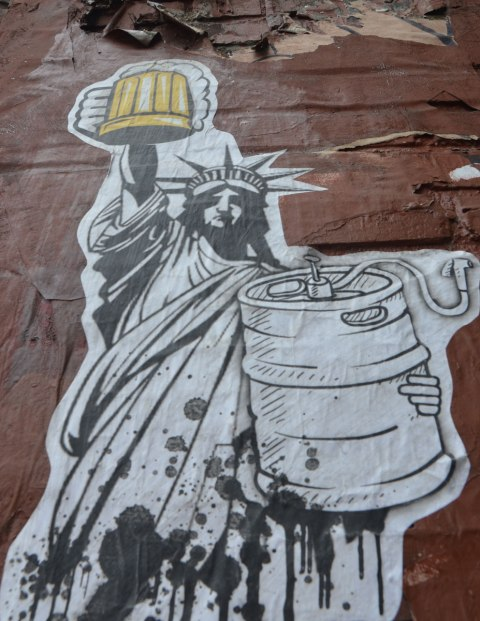 paste up black and white line drawing of the statue of liberty, lady liberty, holding up a yellow coloured beer mug full of beer while holding a large beer keg in the other arm.