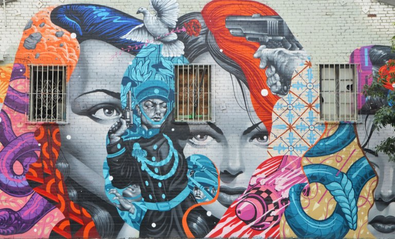 part of a larger mural, two women's faces with a man in a black and blue outit between thwm, a white dove is strating to take flight between their foreheads, a pistol is aimed at the dove,