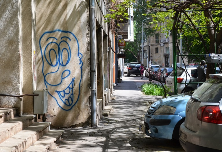 on the side of a building, a blue outline of a man's face, cars parked on the street, trees,