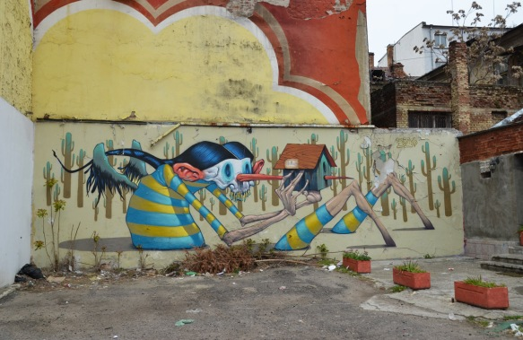 mural by Bozko on a wall in Sofia, a wooden person-like creatire with a long nose is holding a bird house, his nose pierces the bird house.